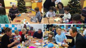 Rodzice i uczniowie wykonują ozdoby świąteczne podczas warsztatów bożonarodzeniowych.