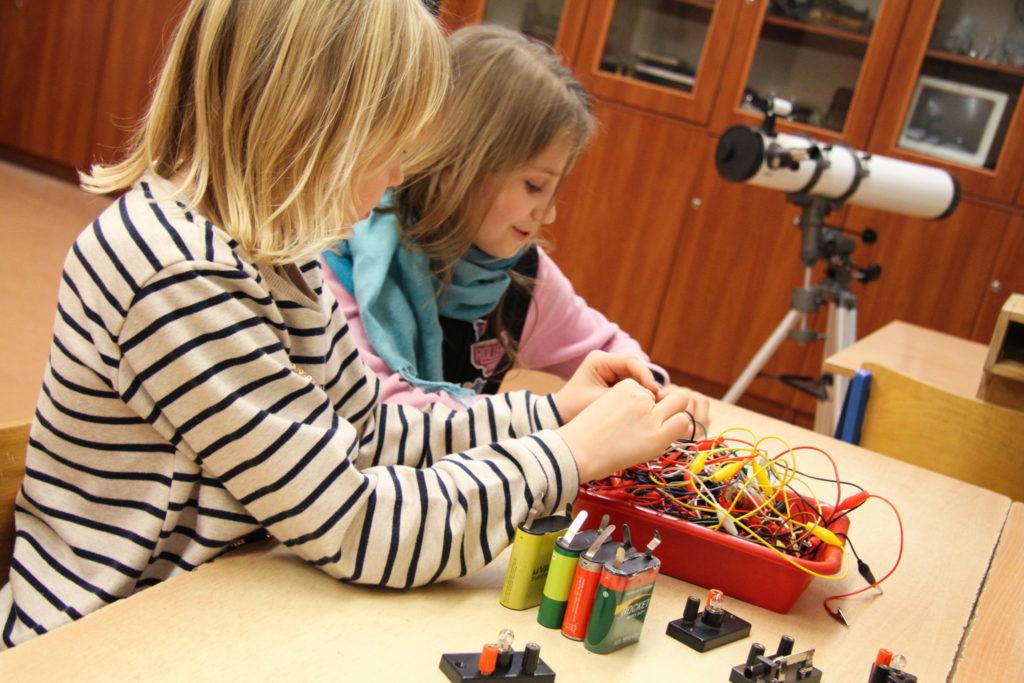 Dwie uczennice siedzą przy stole w pracowni fizycznej. Przewodami łączą baterie z żarówkami.
